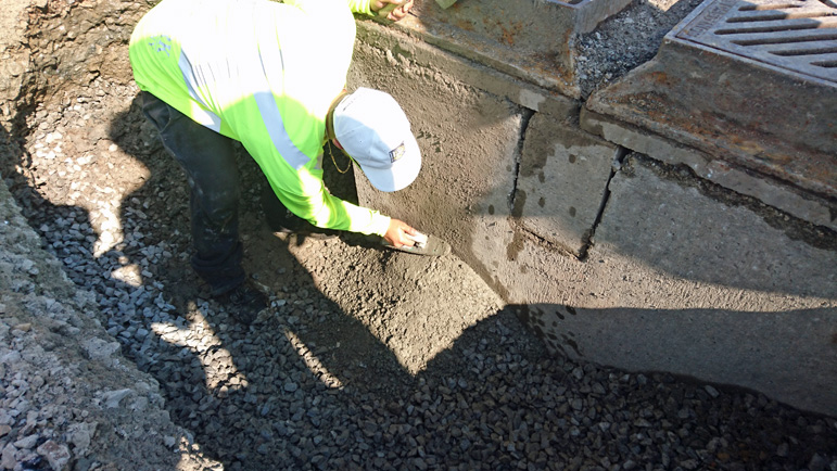 paving contractor fixing a catch basin